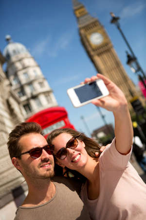 Tourists taking a picture in London with their phone  photo