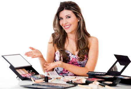 Female makeup artist with a bunch of products - isolated over white photo