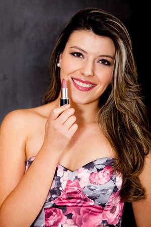 Beautiful woman wearing makeup and holding a lipstick  photo
