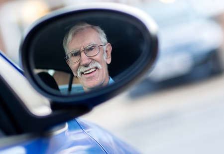 Senior man driving a car and looking himself in the mirror  photo