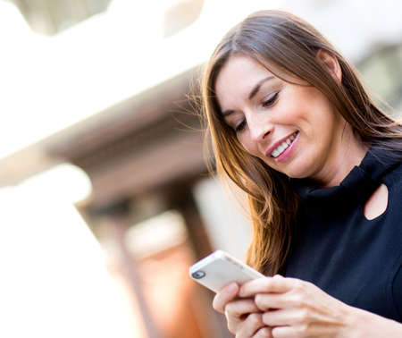 sms text: Woman texting on her cell phone and smiling   Stock Photo