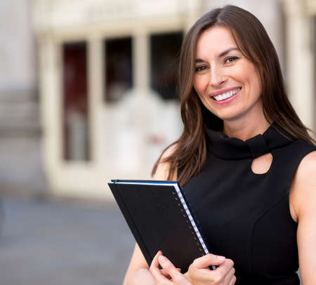 Business woman outdoors holding a folder and smiling  Stock Photo - 15515588