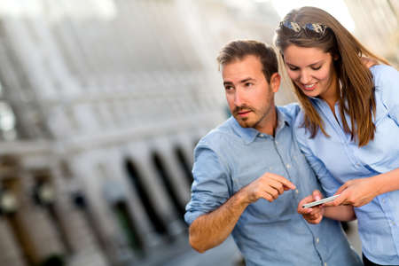 disoriented: Tourists finding a location on their mobile phone with GPS Stock Photo