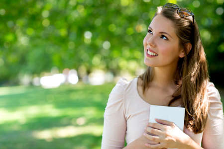 Beautiful portrait of a pensive woman at the park  Stock Photo - 15515586
