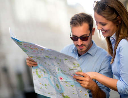 Lost travelers looking at a map and enjoying their holidays  Stock Photo - 15391883