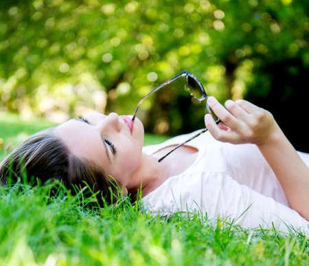 mujer pensando: Mujer pensativa que miente en el parque mirando hacia arriba Foto de archivo