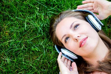 oir: Mujer escuchando m�sica con auriculares en el parque Foto de archivo