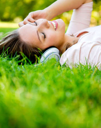 listen music: Woman listening to music with headphones at the park  Stock Photo