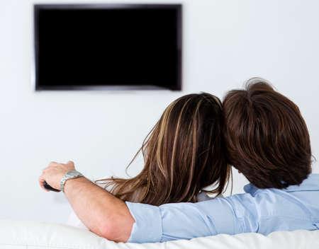 viewing: Coppia guardare la tv a casa in salotto Archivio Fotografico