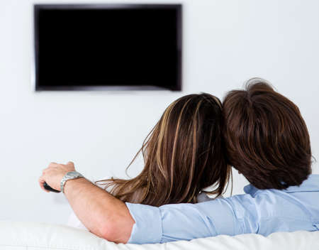 woman watching tv: Pareja viendo la televisi�n en casa, en la sala de estar