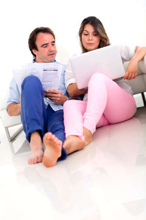 Casual couple discussing their home finances looking upset  photo