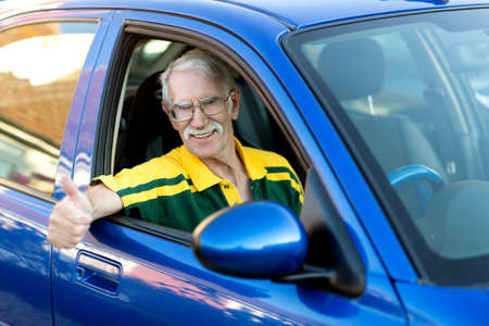 Senior man driving a car and looking very happy  photo