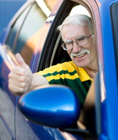 Happy senior man with thumbs up driving a car  photo