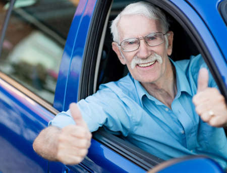 Driving a car: Man driving a car and showing thumbs up