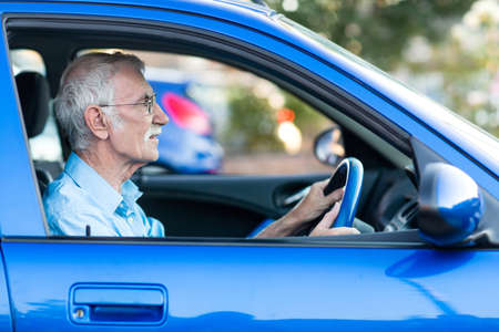 driving: Retired elder man driving a blue car  Stock Photo
