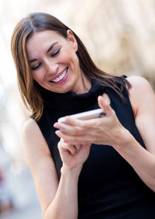 Happy woman sending a text message on her cell phone  Stock Photo - 15458631