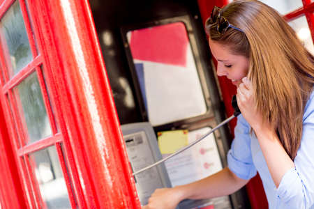 Woman talking on the phone in a telephone booth  photo
