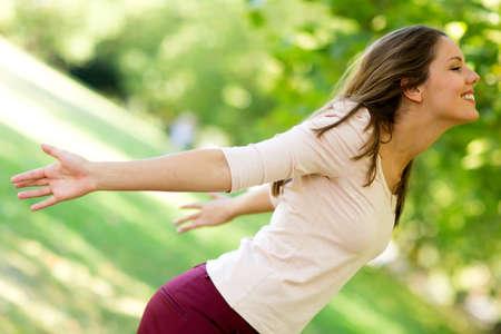 fresh air: Donna con le braccia aperte godere della natura al parco