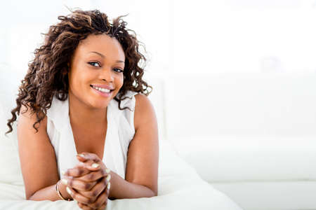 afro hairdo: Beautiful woman at home relaxing in bed  Stock Photo