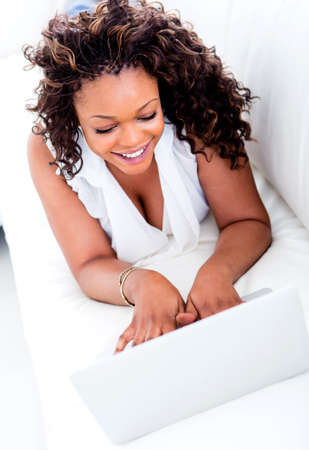 Happy woman working on a laptop computer from home  Stock Photo - 15450646
