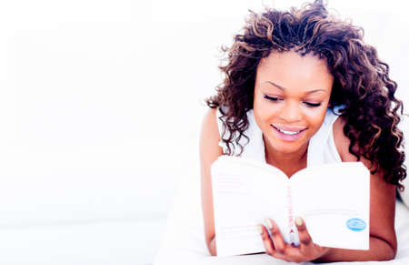 afro hairdo: Beautiful woman enjoying reading a book at home  Stock Photo