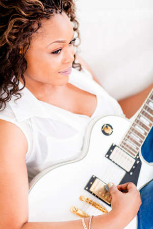 Beautiful black woman playing guitar at home  Stock Photo - 15450656