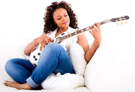 Beautiful woman playing guitar and relaxing at home  photo