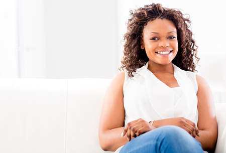 american content: Woman sitting in a sofa at home looking very happy  Stock Photo