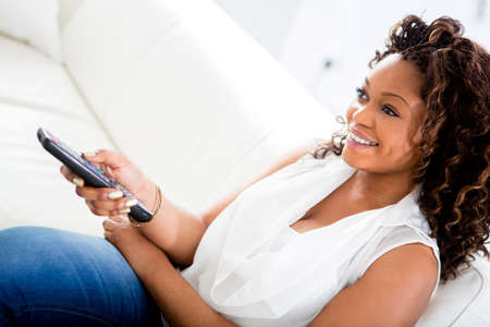 american content: Woman watching television at home looking very happy