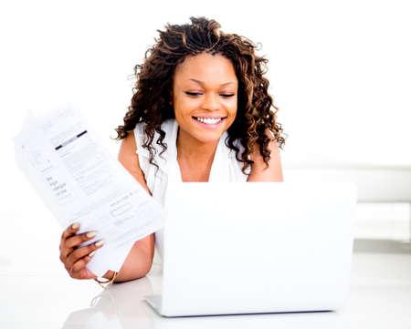 cuenta: La mujer el pago de facturas en línea de casa y sonriente Foto de archivo