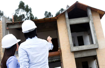 Architects at a construction site pointing at a house  photo