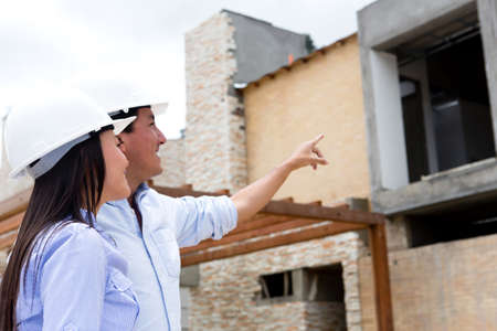 Engineers at a construction site pointing one house  Stock Photo - 15608083