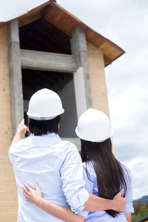 Couple looking at their new house under construction  Stock Photo - 15608088