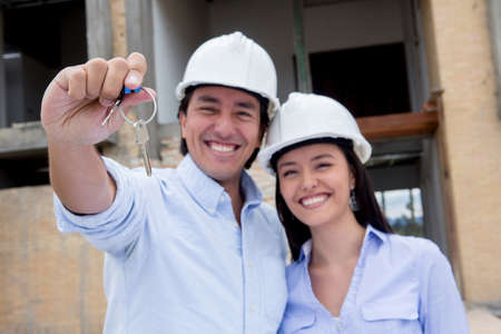 Couple at a construction site holding keys to their new house  photo
