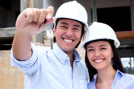 Couple buying a house under construction and holding the keys Stock Photo - 15601160
