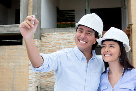 Couple holding a pen and drawing house sketch   Stock Photo - 15601159