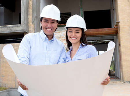 Couple in a construction site looking at their house design  photo