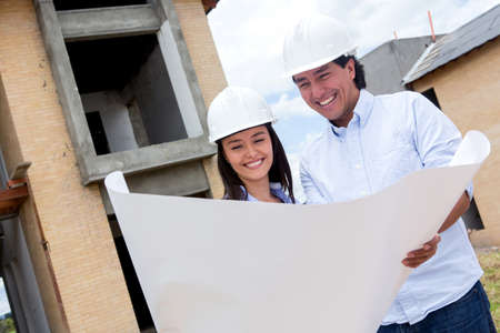 Happy couple building their house and holding blueprints  photo