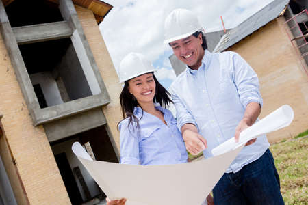 Engineers holding blueprints of a house under construction  Stock Photo - 15574625
