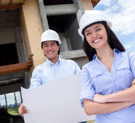 Architects at a construction site holding blueprints  Stock Photo - 15574617