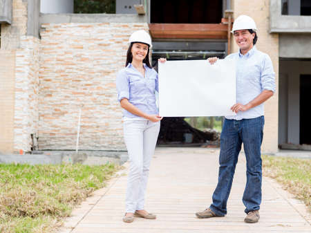 Architects holding banner in a construction site  Stock Photo - 15574619