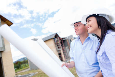 Engineers looking at house project and holding blueprints  Stock Photo - 15574609