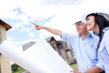 Couple looking at their new house and holding blueprints  photo