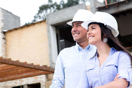construction team: Couple in a construction site looking at house