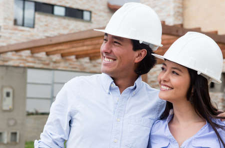 Architects wearing helmets and looking at a house project  photo