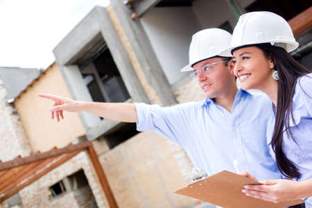 constructor: Civil engineers working in a construction site and pointing away