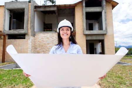 Female architect holding blueprints at a construction site  photo