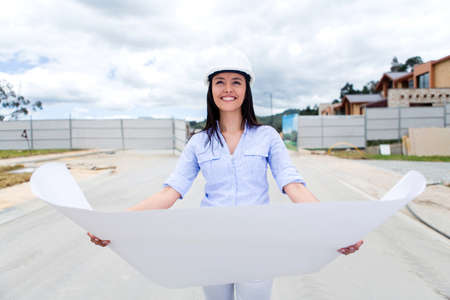 Woman looking at house blueprints in a construction site  photo
