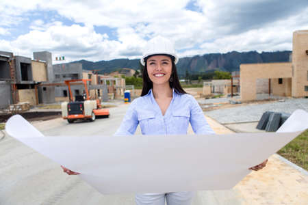female architect: Civil engineer holding blueprints at the building site