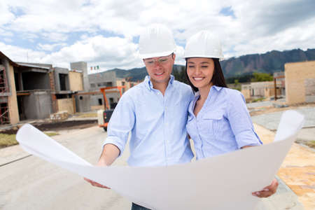 Couple looking at a house project on blueprints  photo